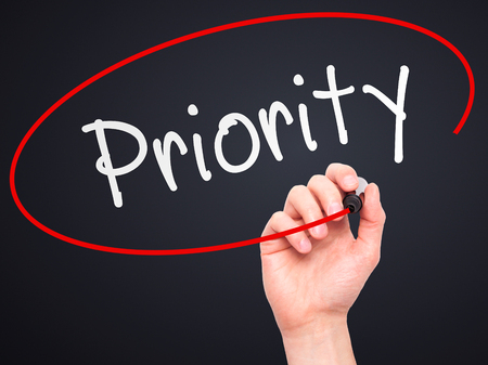 Man Hand writing Priority with marker on transparent wipe board. Isolated on black. Business, internet, technology concept. Stock Photo