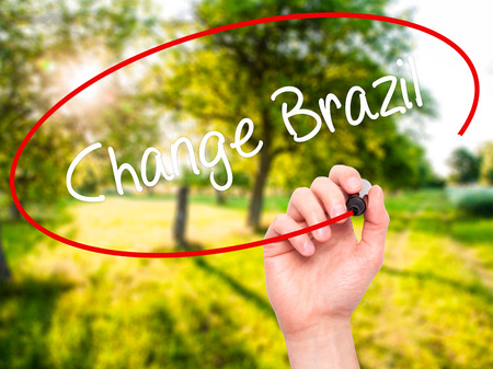 Man Hand writing Change Brazil  with black marker on visual screen. Isolated on nature. Business, technology, internet concept. Stock Photo