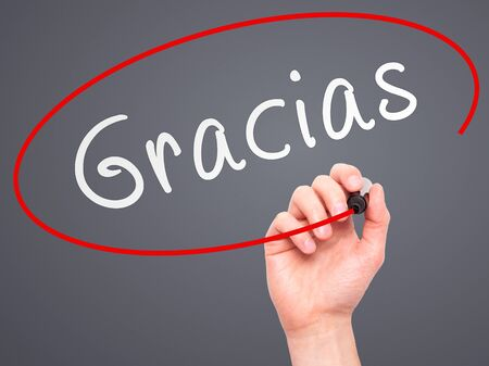 Man Hand writing Gracias with marker on transparent wipe board. Isolated on grey. Business, internet, technology concept.  Stock Photo