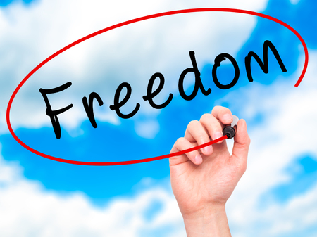 Man Hand writing Freedom with black marker on visual screen. Isolated on sky. Business, technology, internet concept. Stock Image