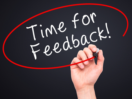 Man Hand writing Time for Feedback with black marker on visual screen. Isolated on black. Business, technology, internet concept. Stock Image