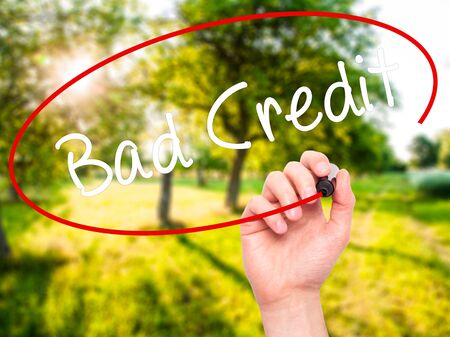 Man Hand writing Bad Credit with black marker on visual screen. Isolated on nature. Business, technology, internet concept. Stock Photo