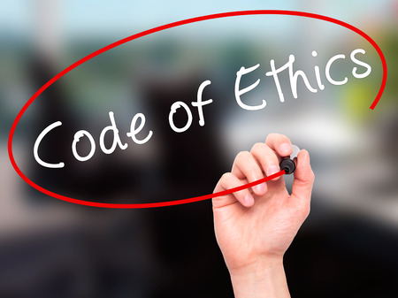 Man Hand writing Code of Ethics with black marker on visual screen. Isolated on office. Business, technology, internet concept. Stock Image