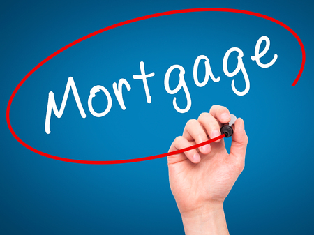 Man Hand writing Mortgage with black marker on visual screen. Isolated on blue. Business, technology, internet concept. Stock Image