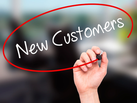 Man Hand writing  New Customers with black marker on visual screen. Isolated on office. Business, technology, internet concept. Stock Photo