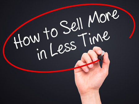 Man Hand writing How to Sell More in Less Time with black marker on visual screen. Isolated on background. Business, technology, internet concept. Stock Photo