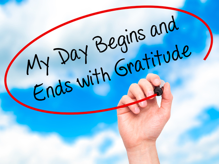 Man Hand writing My Day Begins and Ends with Gratitude with black marker on visual screen. Isolated on sky. Business, technology, internet concept. Stock Photo