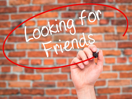 Man Hand writing Looking for Friends with black marker on visual screen. Isolated on background. Business, technology, internet concept. Stock Photo