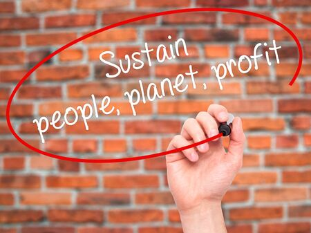 Man Hand writing Sustain, people, planet, profit with black marker on visual screen. Isolated on bricks. Business, technology, internet concept. Stock Photo