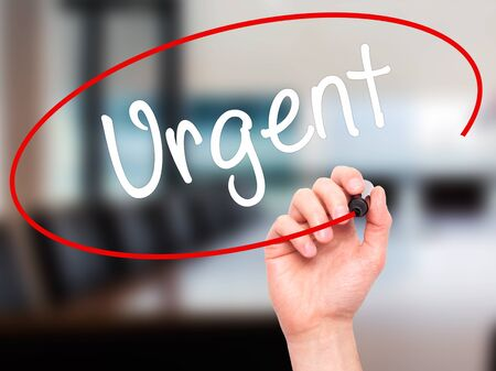 Man Hand writing Urgent  with black marker on visual screen. Isolated on background. Business, technology, internet concept. Stock Photo