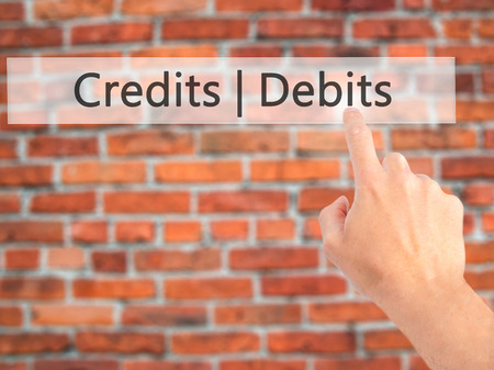 Credits  Debits - Hand pressing a button on blurred background concept . Business, technology, internet concept. Stock Photo