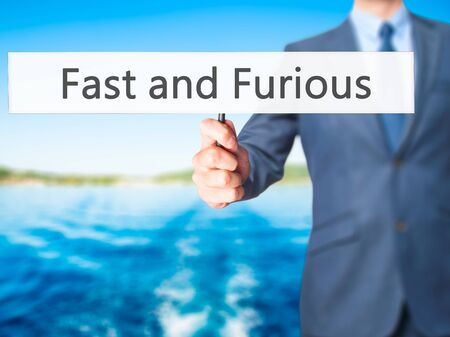 Fast and Furious - Businessman hand holding sign. Business, technology, internet concept. Stock Photo