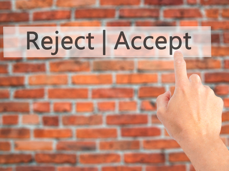 Accept  Reject - Hand pressing a button on blurred background concept . Business, technology, internet concept. Stock Photo