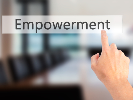 Empowerment - Hand pressing a button on blurred background concept . Business, technology, internet concept. Stock Photo