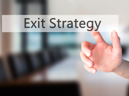 Exit Strategy - Hand pressing a button on blurred background concept . Business, technology, internet concept. Stock Photo