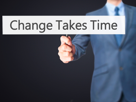 Change Takes Time - Businessman hand holding sign. Business, technology, internet concept. Stock Photo