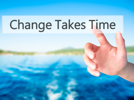 Change Takes Time - Hand pressing a button on blurred background concept . Business, technology, internet concept. Stock Photo