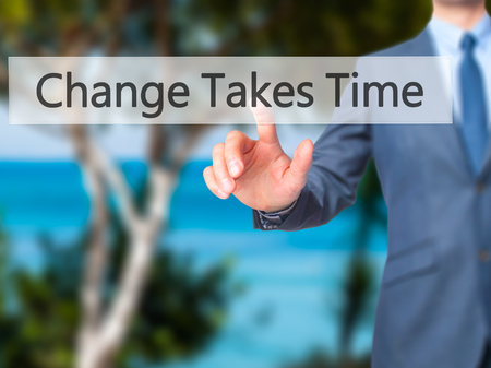 Change Takes Time - Businessman hand pressing button on touch screen interface. Business, technology, internet concept. Stock Photo
