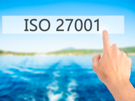 ISO 27001 - Hand pressing a button on blurred background concept . Business, technology, internet concept. Stock Photo
