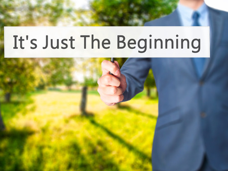 It's Just The Beginning - Businessman hand holding sign. Business, technology, internet concept. Stock Photo