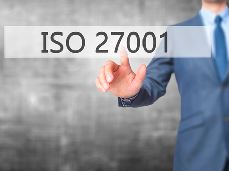 ISO 27001 - Businessman hand pressing button on touch screen interface. Business, technology, internet concept. Stock Photo