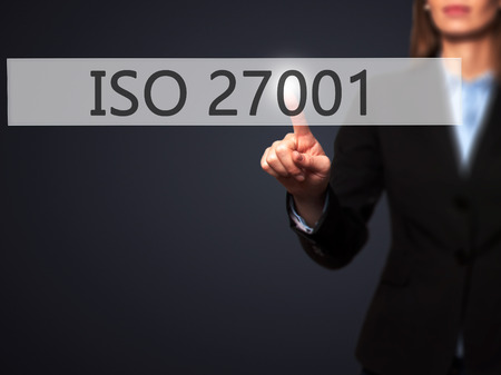 ISO 27001 - Businesswoman hand pressing button on touch screen interface. Business, technology, internet concept. Stock Photo