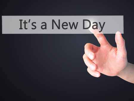 It's a New Day - Hand pressing a button on blurred background concept . Business, technology, internet concept. Stock Photo