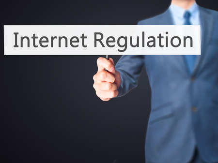 Internet Regulation - Businessman hand holding sign. Business, technology, internet concept. Stock Photo
