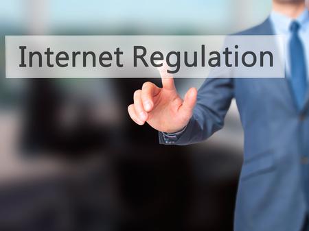 Internet Regulation - Businessman hand pressing button on touch screen interface. Business, technology, internet concept. Stock Photo
