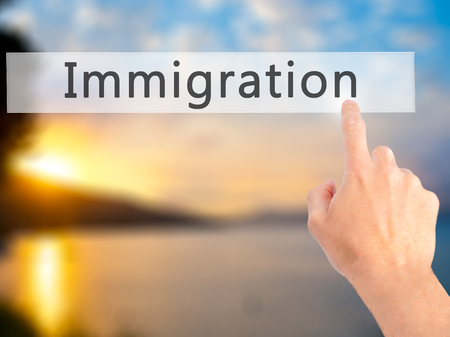 Immigration - Hand pressing a button on blurred background concept . Business, technology, internet concept. Stock Photo