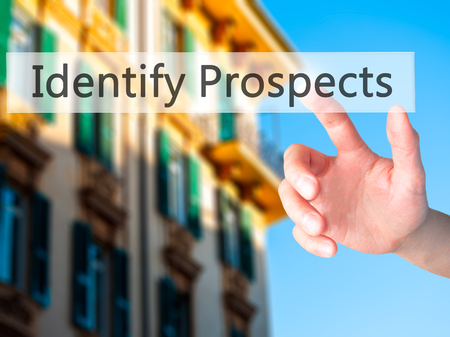 Identify Prospects  - Hand pressing a button on blurred background concept . Business, technology, internet concept. Stock Photo