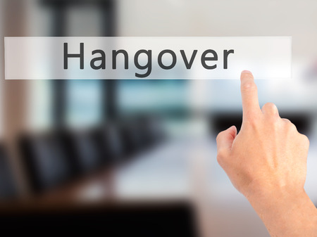 Hangover - Hand pressing a button on blurred background concept . Business, technology, internet concept. Stock Photo