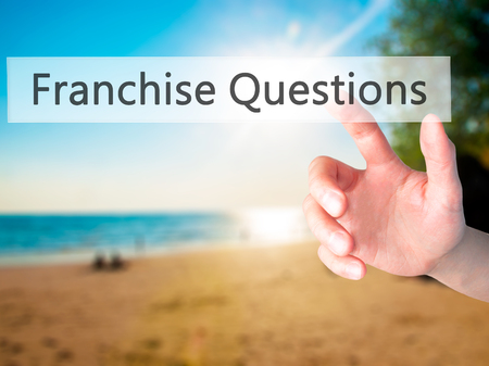 Franchise Questions - Hand pressing a button on blurred background concept . Business, technology, internet concept. Stock Photo