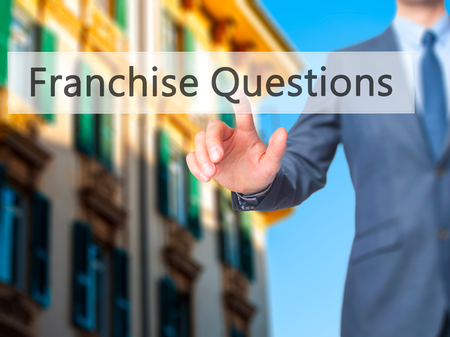 Franchise Questions - Businessman hand pressing button on touch screen interface. Business, technology, internet concept. Stock Photo