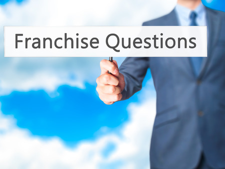 Franchise Questions - Businessman hand holding sign. Business, technology, internet concept. Stock Photo
