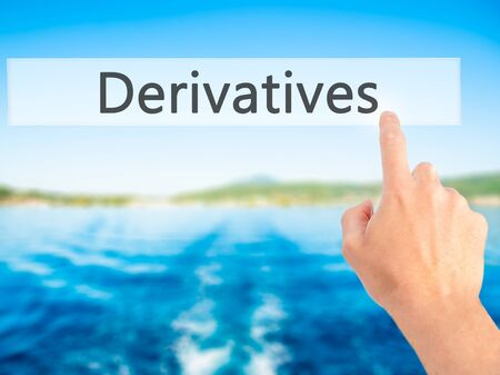 Derivatives - Hand pressing a button on blurred background concept . Business, technology, internet concept. Stock Photo