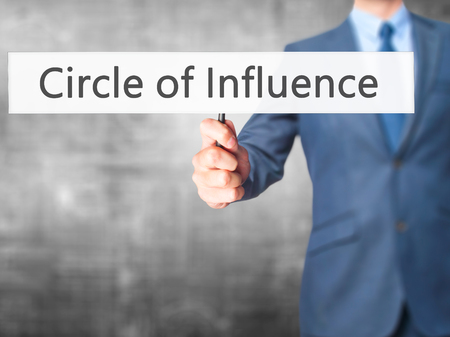 Circle of Influence - Businessman hand holding sign. Business, technology, internet concept. Stock Photo