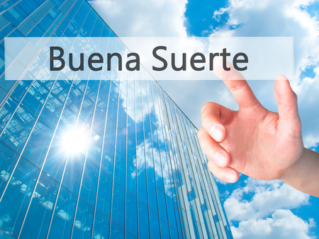 Buena Suerte ( Good Luck in Spanish) - Hand pressing a button on blurred background concept . Business, technology, internet concept. Stock Photo