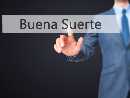Buena Suerte ( Good Luck in Spanish) - Businessman click on virtual touchscreen. Business and IT concept. Stock Photo