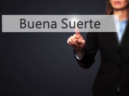 Buena Suerte ( Good Luck in Spanish) - Businesswoman pressing high tech  modern button on a virtual background. Business, technology, internet concept. Stock Photo