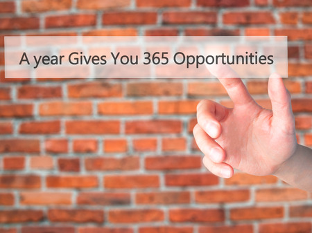 A year Gives You 365 Opportunities - Hand pressing a button on blurred background concept . Business, technology, internet concept. Stock Photo