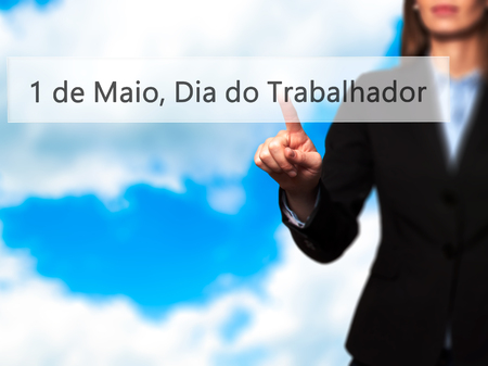 1 de Maio, Dia do Trabalhador (In Portuguese: 1 May, Labor Day) - Isolated female hand touching or pointing to button. Business and future technology concept. Stock Photo