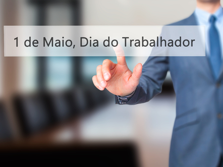 1 de Maio, Dia do Trabalhador (In Portuguese: 1 May, Labor Day) - Businessman press on digital screen. Business, internet concept. Stock Photo