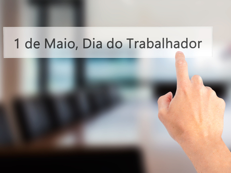 1 de Maio, Dia do Trabalhador (In Portuguese: 1 May, Labor Day) - Hand pressing a button on blurred background concept . Business, technology, internet concept. Stock Photo