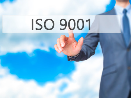 ISO 9001 - Businessman hand pressing button on touch screen interface. Business, technology, internet concept. Stock Photo