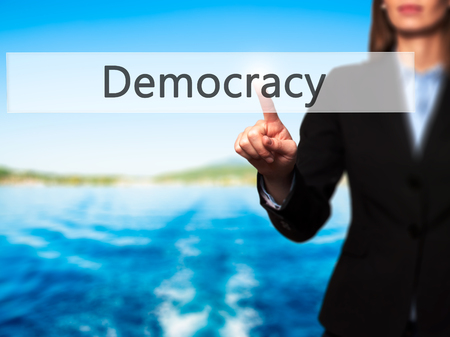Democracy - Isolated female hand touching or pointing to button. Business and future technology concept. Stock Photo
