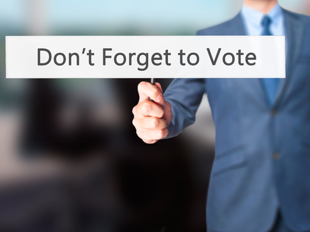 Don't Forget to Vote - Businessman hand holding sign. Business, technology, internet concept. Stock Photo