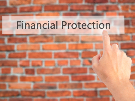 Financial Protection - Hand pressing a button on blurred background concept . Business, technology, internet concept. Stock Photo