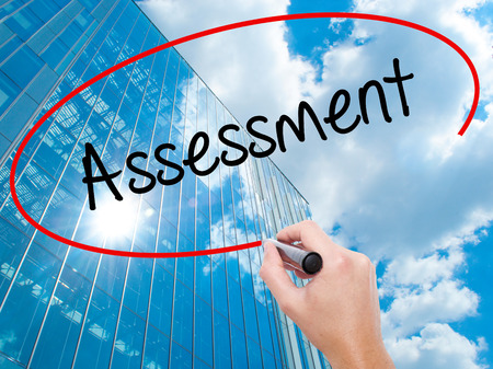Man Hand writing Assessment with black marker on visual screen. Business, technology, internet concept. Modern business skyscrapers background. Stock Photo