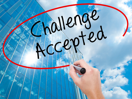 Man Hand writing  Challenge Accepted with black marker on visual screen. Business, technology, internet concept. Modern business skyscrapers background. Stock Photo